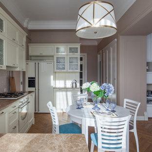 Пример оригинального дизайна интерьера: п-образная кухня-гостиная в стиле современная классика с накладной раковиной, фасадами с утопленной филенкой, белыми фасадами, бежевым фартуком, белой техникой, паркетным полом среднего тона, коричневым полом и коричневой столешницей