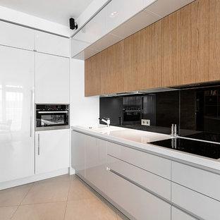 Удачное сочетание для дизайна помещения: маленькая угловая кухня-гостиная в современном стиле с плоскими фасадами, белыми фасадами, черным фартуком и техникой под мебельный фасад без острова - самое интересное для вас