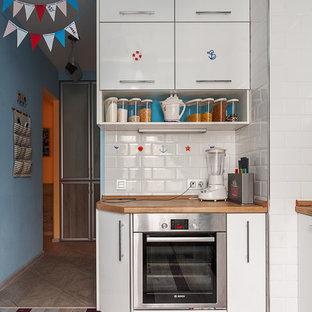 На фото: маленькая отдельная, угловая кухня в морском стиле с плоскими фасадами, белыми фасадами, белым фартуком, фартуком из плитки кабанчик, техникой из нержавеющей стали, столешницей из дерева и деревянным полом с