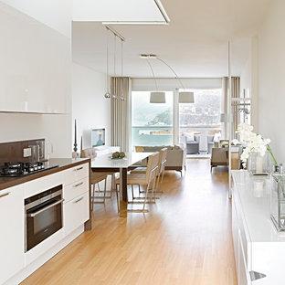 Immagine di una cucina minimal di medie dimensioni con ante lisce, ante bianche, elettrodomestici neri, parquet chiaro e top in superficie solida