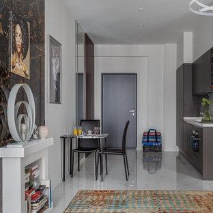Пример оригинального дизайна интерьера: линейная кухня-гостиная в современном стиле с плоскими фасадами, серыми фасадами, белым фартуком, черной техникой и белым полом без острова