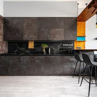 На фото: большие угловые кухни-гостиные в современном стиле с мраморной столешницей, черным фартуком, фартуком из мрамора, полом из ламината, серым полом, черной столешницей, плоскими фасадами, серыми фасадами и полуостровом