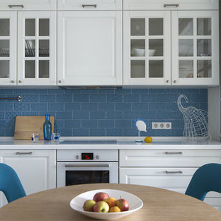 他の地域の小さいコンテンポラリースタイルのおしゃれなキッチン (レイズドパネル扉のキャビネット、白いキャビネット、人工大理石カウンター、青いキッチンパネル、セラミックタイルのキッチンパネル、白い調理設備、セラミックタイルの床、アイランドなし、青い床、ドロップインシンク) の写真