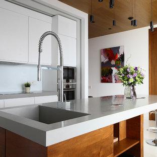 На фото: с высоким бюджетом параллельные кухни-гостиные среднего размера в современном стиле с плоскими фасадами, белыми фасадами, столешницей из кварцита, белым фартуком, фартуком из стекла, техникой из нержавеющей стали, островом и монолитной раковиной