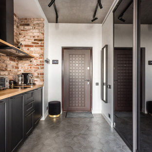 Свежая идея для дизайна: линейная кухня в стиле лофт с накладной раковиной, фасадами с утопленной филенкой, черными фасадами, коричневым фартуком, фартуком из кирпича, серым полом и коричневой столешницей - отличное фото интерьера