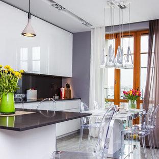 Идея дизайна: большая угловая кухня в современном стиле с паркетным полом среднего тона, обеденным столом, врезной раковиной, плоскими фасадами, белыми фасадами, черным фартуком и серым полом