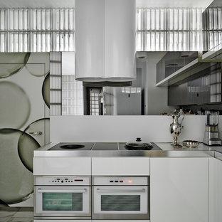 Удачное сочетание для дизайна помещения: кухня в современном стиле с плоскими фасадами, белыми фасадами, столешницей из нержавеющей стали, белым фартуком, белой техникой, серым полом, фартуком из зеркальной плитки и серой столешницей - самое интересное для вас