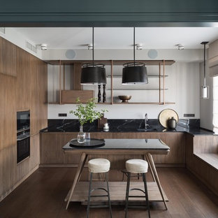Contemporary enclosed kitchen ideas - Trendy u-shaped medium tone wood floor and brown floor enclosed kitchen photo in Moscow with an undermount sink, flat-panel cabinets, medium tone wood cabinets, black backsplash, black appliances, an island and black countertops