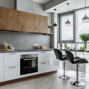 Новые идеи обустройства дома: линейная кухня в современном стиле с плоскими фасадами, белыми фасадами, серым фартуком, черной техникой, бежевым полом и серой столешницей