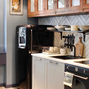 Modelo de cocina lineal, bohemia, pequeña, abierta, con fregadero encastrado, puertas de armario grises, salpicadero verde, electrodomésticos negros y suelo de madera clara