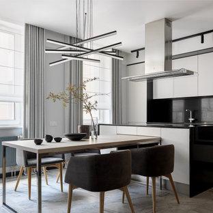Идея дизайна: кухня в современном стиле с обеденным столом, плоскими фасадами, белыми фасадами, черным фартуком, островом, серым полом и черной столешницей