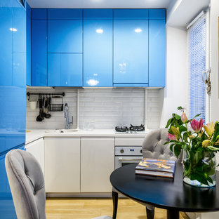 Inspiration for a contemporary l-shaped kitchen in Moscow with flat-panel cabinets, blue cabinets, white splashback, subway tile splashback, white appliances, no island, light hardwood floors and beige floor.