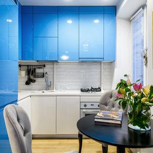 На фото: угловая кухня в современном стиле с плоскими фасадами, синими фасадами, белым фартуком, фартуком из плитки кабанчик, белой техникой, светлым паркетным полом и бежевым полом без острова