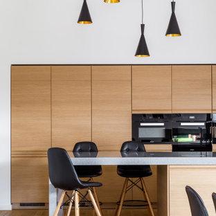 Свежая идея для дизайна: параллельная кухня-гостиная среднего размера в современном стиле с плоскими фасадами, фасадами цвета дерева среднего тона, техникой под мебельный фасад, островом, бежевым полом и серой столешницей - отличное фото интерьера