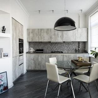 Пример оригинального дизайна интерьера: угловая кухня-гостиная в современном стиле с плоскими фасадами, серыми фасадами, серым фартуком, черной техникой, темным паркетным полом, черным полом и серой столешницей без острова