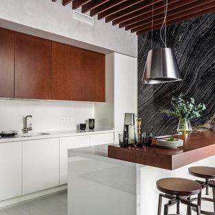 Идея дизайна: параллельная кухня в современном стиле с монолитной раковиной, плоскими фасадами, темными деревянными фасадами, техникой под мебельный фасад, светлым паркетным полом, полуостровом и белой столешницей