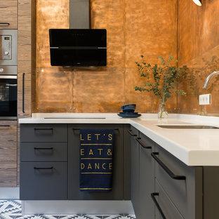Пример оригинального дизайна: угловая кухня-гостиная среднего размера в современном стиле с врезной раковиной, плоскими фасадами, серыми фасадами, столешницей из акрилового камня, фартуком из стекла, техникой из нержавеющей стали, полом из цементной плитки, разноцветным полом и оранжевым фартуком без острова