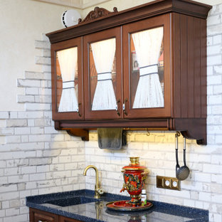 Inspiration for a small traditional single-wall separate kitchen in Other with an integrated sink, raised-panel cabinets, dark wood cabinets, solid surface benchtops, white splashback, porcelain splashback, porcelain floors, no island, blue floor, blue benchtop and timber.