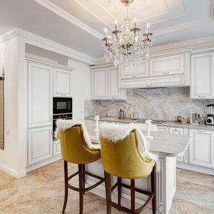 Новые идеи обустройства дома: угловая кухня среднего размера в классическом стиле с фасадами с выступающей филенкой, белыми фасадами, серым фартуком, черной техникой, островом, бежевым полом, серой столешницей и накладной раковиной