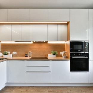 サンクトペテルブルクの中くらいのコンテンポラリースタイルのおしゃれなL型キッチン (ドロップインシンク、フラットパネル扉のキャビネット、白いキャビネット、木材カウンター、茶色いキッチンパネル、木材のキッチンパネル、パネルと同色の調理設備、アイランドなし、茶色い床、ベージュのキッチンカウンター) の写真