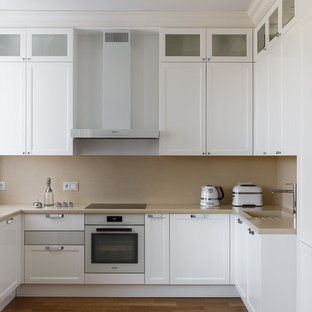 Свежая идея для дизайна: п-образная кухня в стиле современная классика с монолитной раковиной, фасадами с утопленной филенкой, белыми фасадами, бежевым фартуком, белой техникой, паркетным полом среднего тона, коричневым полом и бежевой столешницей - отличное фото интерьера