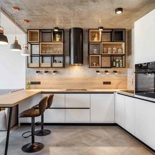 他の地域のコンテンポラリースタイルのおしゃれなキッチン (シングルシンク、フラットパネル扉のキャビネット、白いキャビネット、木材カウンター、ベージュキッチンパネル、ガラスまたは窓のキッチンパネル、黒い調理設備、コンクリートの床、グレーの床、ベージュのキッチンカウンター) の写真