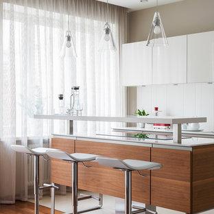 Пример оригинального дизайна: кухня в современном стиле с плоскими фасадами, белым фартуком, островом, белой столешницей и бежевым полом