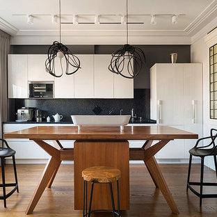 Стильный дизайн: прямая кухня в современном стиле с островом, плоскими фасадами, белыми фасадами, черным фартуком, коричневым полом, обеденным столом, врезной раковиной, деревянной столешницей, техникой под мебельный фасад и паркетным полом среднего тона - последний тренд