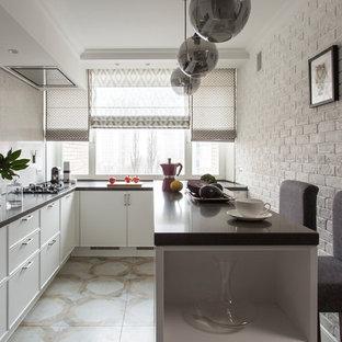 Новый формат декора квартиры: отдельная, п-образная кухня в стиле современная классика с врезной раковиной, фасадами с декоративным кантом, белыми фасадами, бежевым фартуком, полуостровом и бежевым полом
