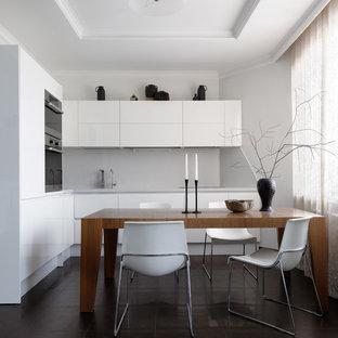 На фото: угловая кухня в современном стиле с обеденным столом, плоскими фасадами, белыми фасадами и черной техникой