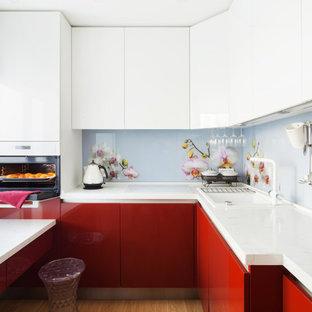 Modelo de cocina en L, actual, pequeña, sin isla, con fregadero encastrado, armarios con paneles lisos, puertas de armario rojas, salpicadero multicolor, salpicadero de vidrio templado y suelo marrón
