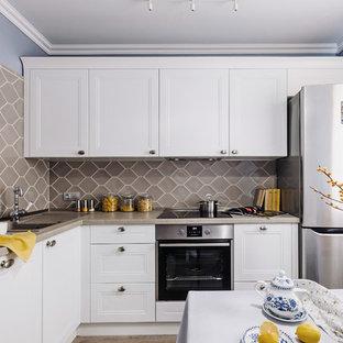 Источник вдохновения для домашнего уюта: маленькая угловая кухня со шкафом над холодильником в скандинавском стиле с обеденным столом, накладной раковиной, фасадами с утопленной филенкой, белыми фасадами, столешницей из ламината, серым фартуком, фартуком из керамической плитки, техникой из нержавеющей стали, полом из ламината, серым полом и серой столешницей без острова