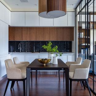 Свежая идея для дизайна: угловая кухня в современном стиле с черным фартуком, коричневым полом и плоскими фасадами - отличное фото интерьера