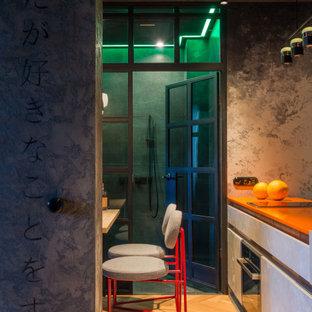 Ispirazione per una piccola cucina industriale con lavello integrato, ante lisce, ante con finitura invecchiata, top in quarzo composito, paraspruzzi grigio, elettrodomestici neri, pavimento in legno massello medio, penisola e top arancione