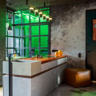 Inspiration för ett litet funkis orange oranget kök, med en integrerad diskho, släta luckor, skåp i slitet trä, bänkskiva i kvarts, grått stänkskydd, svarta vitvaror, mellanmörkt trägolv och en halv köksö