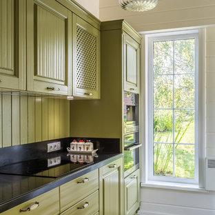 Неиссякаемый источник вдохновения для домашнего уюта: маленькая прямая кухня в классическом стиле с зелеными фасадами, мраморной столешницей, черной техникой, полом из керамической плитки, фасадами с выступающей филенкой, зеленым фартуком, фартуком из дерева и разноцветным полом