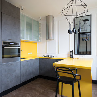 Новые идеи обустройства дома: п-образная кухня в современном стиле с врезной раковиной, плоскими фасадами, серыми фасадами, желтым фартуком, техникой из нержавеющей стали, темным паркетным полом, полуостровом, коричневым полом и желтой столешницей