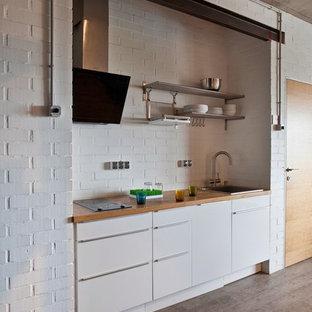 モスクワのコンテンポラリースタイルのおしゃれなキッチン (ドロップインシンク、フラットパネル扉のキャビネット、白いキャビネット、白いキッチンパネル、レンガのキッチンパネル、アイランドなし) の写真
