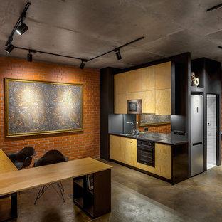 Идея дизайна: прямая кухня-гостиная в стиле лофт с плоскими фасадами, светлыми деревянными фасадами, черной столешницей, врезной раковиной, фартуком из стекла, черной техникой, бетонным полом и коричневым полом без острова