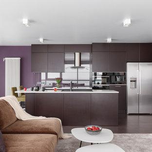 На фото: большие параллельные кухни-гостиные в современном стиле с накладной раковиной, плоскими фасадами, коричневыми фасадами, фартуком из стекла, техникой из нержавеющей стали, островом, коричневым полом и белой столешницей