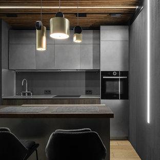 На фото: кухни в современном стиле с монолитной раковиной, плоскими фасадами, серыми фасадами, серым фартуком, островом, коричневым полом и серой столешницей