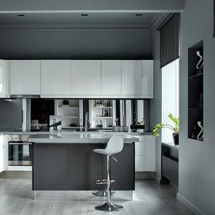 На фото: угловая кухня-гостиная в современном стиле с плоскими фасадами, белыми фасадами, фартуком из стекла, техникой из нержавеющей стали, светлым паркетным полом, островом, серым полом и серой столешницей с