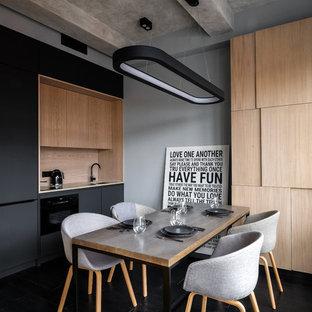 На фото: маленькая прямая кухня в современном стиле с врезной раковиной, плоскими фасадами, черными фасадами, бежевым фартуком, черной техникой, черным полом и акцентной стеной с