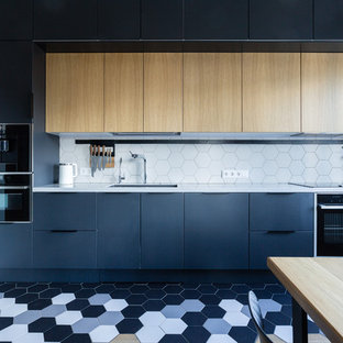 This is an example of a large contemporary single-wall eat-in kitchen in Moscow with an undermount sink, flat-panel cabinets, black cabinets, quartz benchtops, white splashback, ceramic splashback, black appliances, ceramic floors, no island, white benchtop and multi-coloured floor.