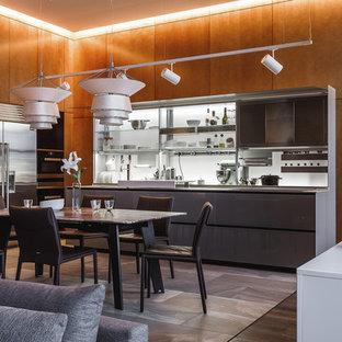 На фото: угловая кухня-гостиная в современном стиле с плоскими фасадами, серыми фасадами, белым фартуком, техникой из нержавеющей стали и серым полом без острова с