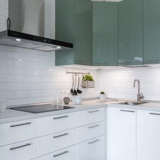 На фото: угловая кухня в скандинавском стиле с плоскими фасадами, зелеными фасадами, белым фартуком, фартуком из плитки кабанчик, черной техникой и белой столешницей с