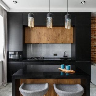 Свежая идея для дизайна: параллельная кухня в стиле лофт с врезной раковиной, плоскими фасадами, черными фасадами, серым фартуком, черной техникой, островом, серым полом и черной столешницей - отличное фото интерьера