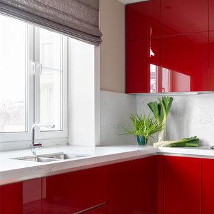 Источник вдохновения для домашнего уюта: угловая кухня с врезной раковиной, плоскими фасадами, красными фасадами, белым фартуком, серым полом и белой столешницей