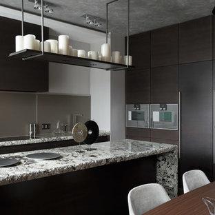 Пример оригинального дизайна: угловая кухня-гостиная в современном стиле с плоскими фасадами, темными деревянными фасадами, серым фартуком, техникой из нержавеющей стали и островом