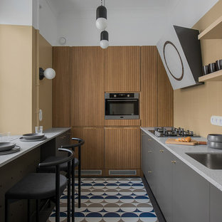 Ejemplo de cocina en L, minimalista, pequeña, cerrada, sin isla, con fregadero bajoencimera, armarios con paneles lisos, puertas de armario grises, salpicadero beige, electrodomésticos de acero inoxidable, suelo multicolor, encimeras grises y encimera de terrazo